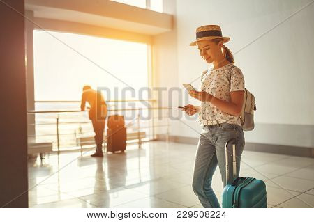 Young Woman Waiting For  Flying  At Airport  At Window  With A Suitcase