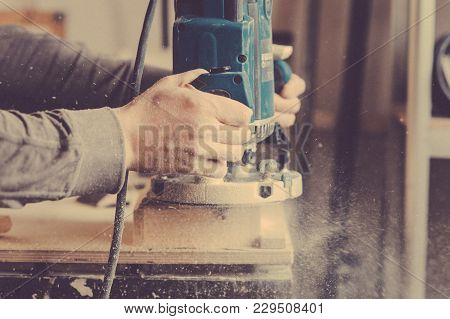 Processing Of A Furniture Part By A Machine For Polishing A Wooden Furniture Detail. Toned Image.