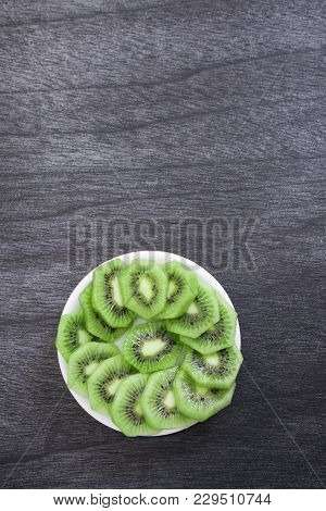 Fresh sliced kiwi on plate. Green Kiwi fruit slices on dark wooden background. Copy space. Kiwi cute