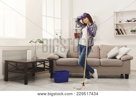 Young Woman Tired Of Spring Cleaning House, Washing Floor With Mop, Copy Space