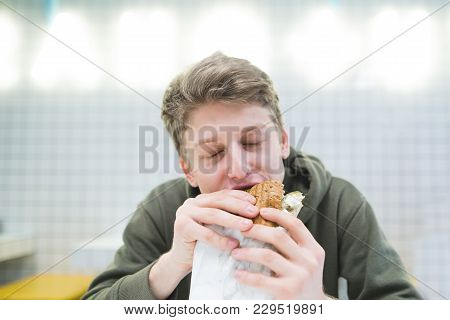A Young Man Bites A Delicious Hamburger In A Light Restaurant. Hungry Student Eats Hamburger With Pl