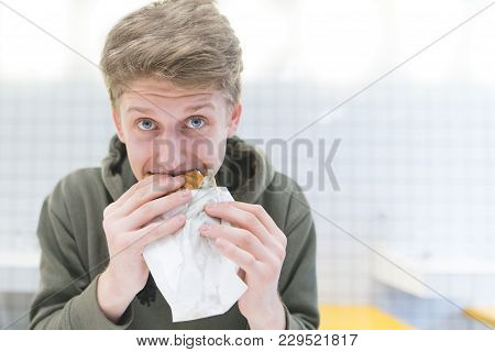 A Funny Young Student Bites A Sandwich And Looks At The Camera. Portrait Of A Young Man Eating A Ham