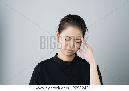 Woman In A Black Dress Is Touching Head To Show Her Headache. Causes May Be Caused By Stress Or Migr