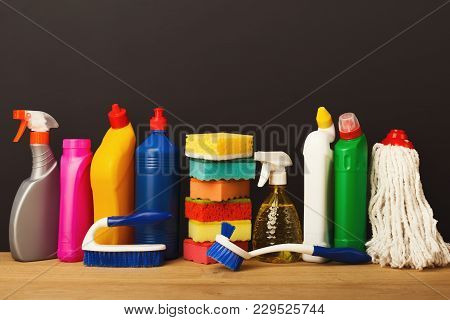 Group Of Colorful Cleaning Products On Dark Background. Different Bottles, Sponges, Brushes And Mop