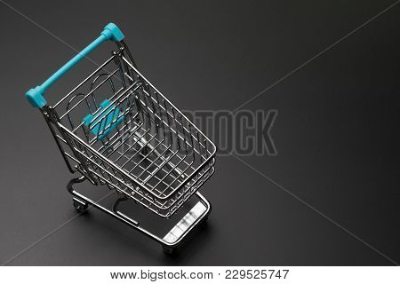 Top View Of Empty Shopping Cart With Blue Handle On Dark Black Background With Copy Space.