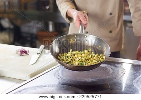 Chef Holding Frying Pan With Sliced Vegetables. Male Chef Holding In Hands Stainless Frying Pan With