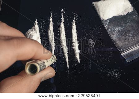 Drug Abuse. Hand Of Man Holds Rolled Banknote For Snorting Line Of Cocaine Powder. Problems With Dru