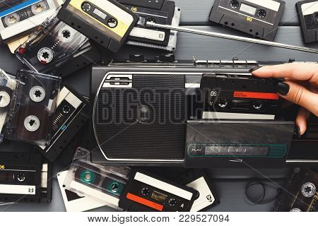 Heap Of Retro Audio Cassettes And Vintage Tape Recorder On Gray Background. Top View On Old-fashione