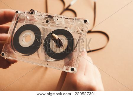 Hands Rewinding Magnetic Tape Audio Cassette On Pencil. Closeup Of Vintage Tape And Simple Device Fo