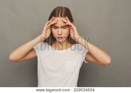 Portrait Of Young Woman Having Headache. Attractive Girl With Migraine Touching Her Head, Grey Backg