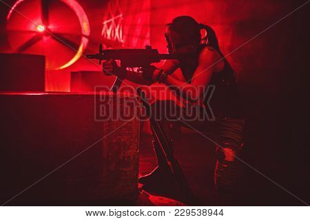 Young strong woman warrior shooting from machine gun in dramatic urban night red colors scene. Tattoo on body.