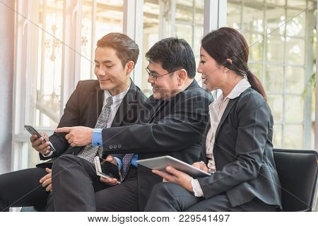 Bussiness Team Looking And Smiling Content At Cell Phone