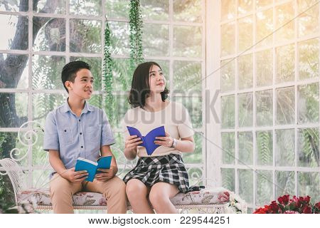 Sister And Young Brother Smiling And Reading In Glass House