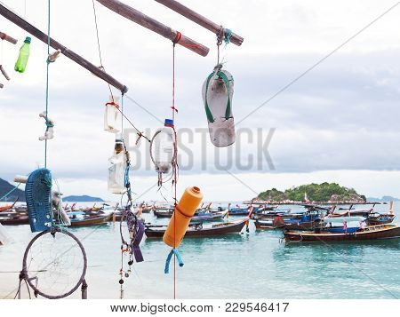 Mobile Garbage From The Sea Hanging On Bamboo Timber At Summer Beach Over Fishing Boat Background. C