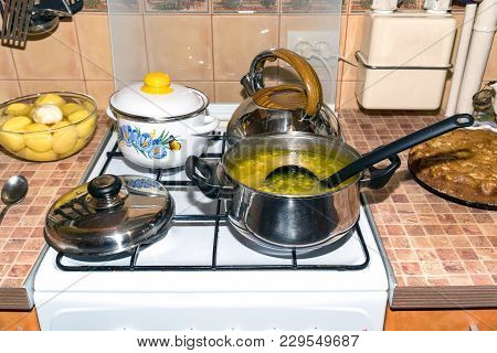 Soup In A Saucepan And Cooking Utensils On A Gas Stove. In The Saucepan With Soup Ladle. On The Stov