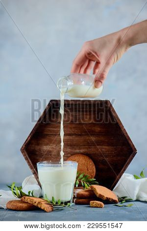 Hand Pouring Milk In A Glass. Cookies In A Wooden Tray. High Key Food Photography On A Concrete Back