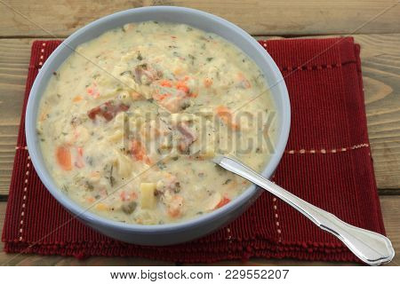 Porcelain Blue Bowl Full With Fresh Slow Cooked Cream Soup On Red Placemat Over Wooden Table, Soup I