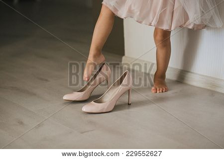 A Little Girl In A Dress Wearing Foot Adult Mum's High-heeled Shoes. Close-up