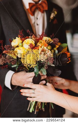 A Beautiful Autumn Wedding Bouquet In The Hands Of A Stylish Groom In A Brown Suit And An Orange Bow