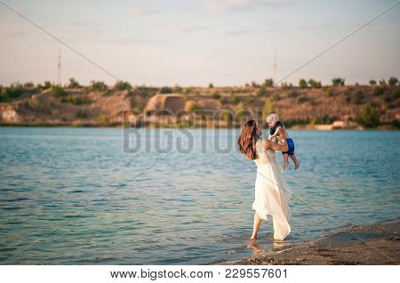 Young Mother With Her Son On The Beach On A Sunset Background. Unplugged Mindfull.