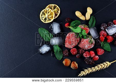 Frozen Raspberry, Blackberry, Strawberries Mint Leaves, Pieces Of Ice On A Black Shale Board, Slices