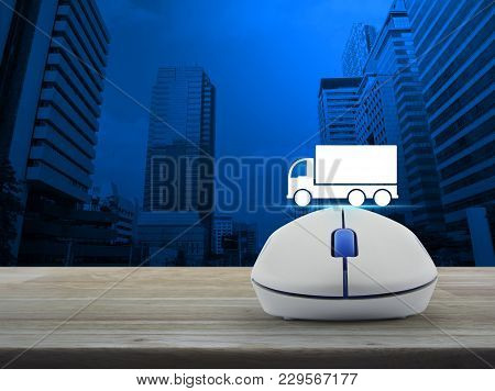 Truck Flat Icon With Wireless Computer Mouse On Wooden Table Over Modern Office City Tower, Business