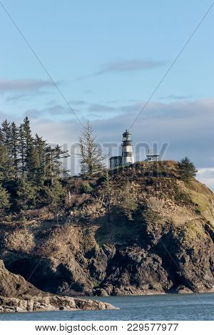 Northhead Lighthouse With Driftwood And Ocean On Bright Winter Day