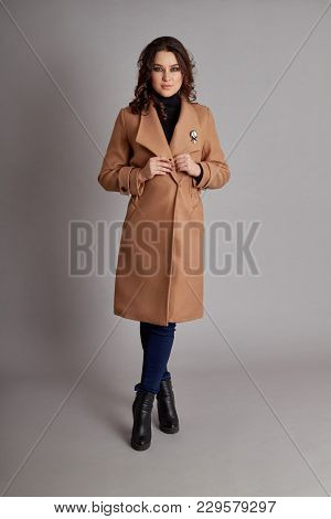 Fashion Girl In Spring Coat On Grey Background, Spring Wear. Bright Coat On A Girl's Body, The Sprin