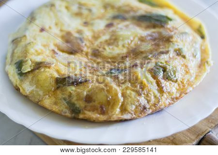 Spanish Potato Omelette On A Kitchen Table With A Wooden Base, Spanish Omelette Is The English Name
