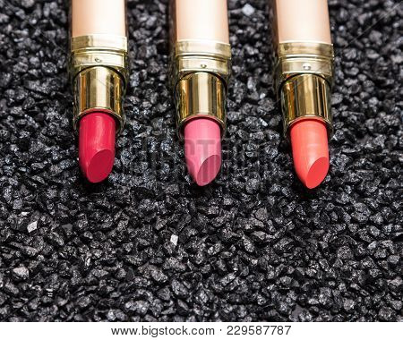 Different Colors Of Lipstick On Anthracite Surface With Copy Space. Close-up, Selective Focus