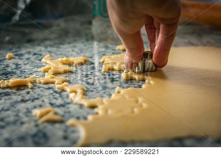 A Hand Making Shapes In An Extended Dough On A Kitchen Table Making Seasonal Pastry Food. Chef Hand
