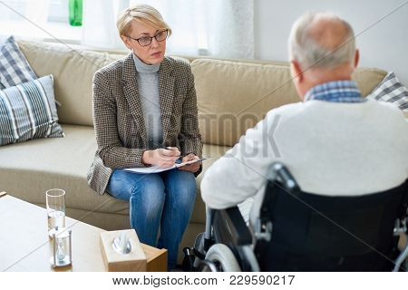 Portrait Of Mature Female Psychiatrist Interviewing Handicapped Senior Man During Therapy Session, C