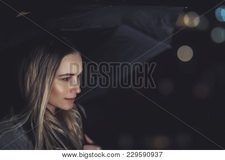 Portrait of a beautiful blond girl waiting for someone at dark rainy night, fashion women's portrait with umbrella over blurry night city lights background