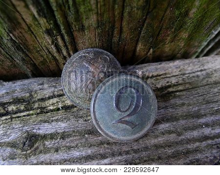 Two Old Buttons On A Wooden Board