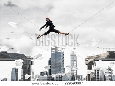Business Woman Jumping Over Gap With Flying Paper Planes In Concrete Bridge As Symbol Of Overcoming