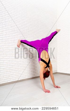 Red-haired Young Girl In A Bright Sports Suit Engaged In Yoga Against A Light Brick Wall