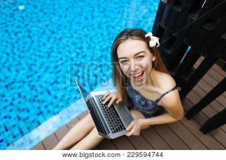 Female Woman Smilling Looking At Camera With Laptop On Background Of Pool, Picture Taken From Above.