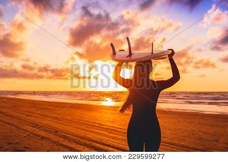 Surf Girl With Long Hair Go To Surfing. Woman With Surfboard On A Beach At Sunset.