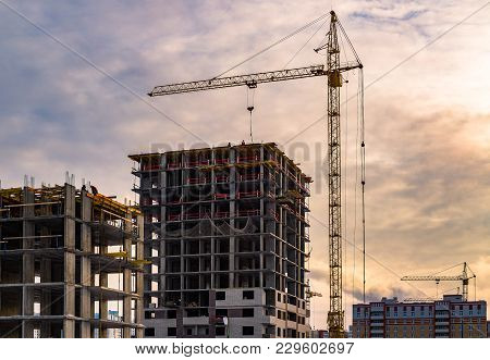 Building Crane And Building Under Construction. Construction Site. Construction Cranes And High Rise