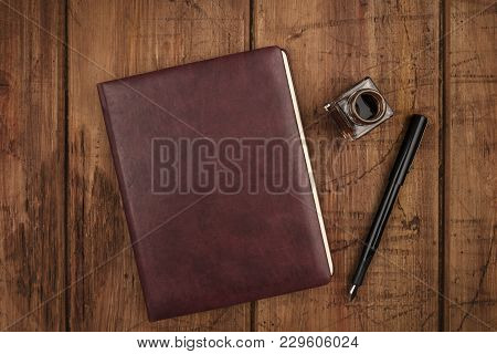 An Overhead Photo Of A Leather Bound Journal, An Ink Well And Pen, Shot From Above On A Dark Rustic