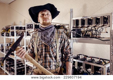 Man As A Gold Prospector With A Tool On The Background Of Computer Devices