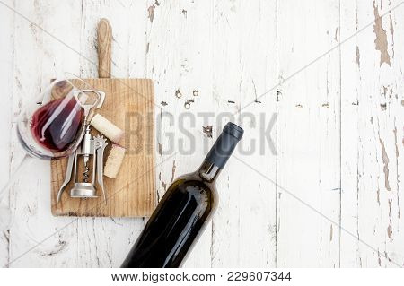 A Glass Of Red Wine, Bottle, Corkscrew  And Wine Corks On Rustic Board Over  White Wooden Table, Cop