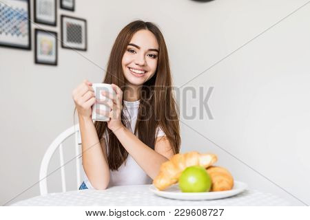 Portrait Of Beautiful Young Woman Having Breakfast In The Kitchen In The Morning