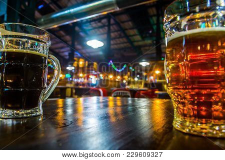 Two Glass Transparent Mugs With Dark And Light Beer On A Pub Background