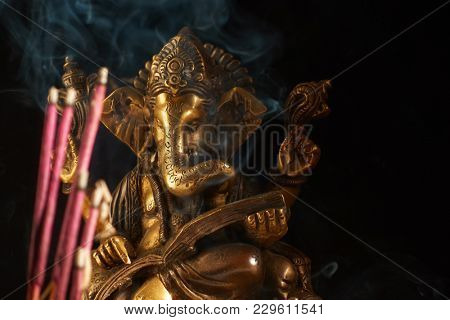 Hindu God Ganesha and smoking incense sticks