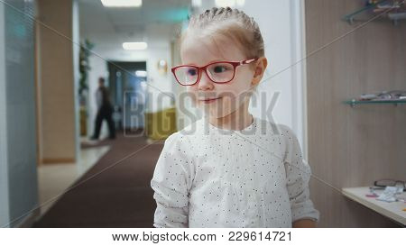 Adorable Child Blonde Girl In Ophthalmology Clinic Plays In Hall Near Glasses Store, Close Up
