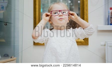 Little Girl Tries New Glasses Near Mirror - Shopping In Ophthalmology Clinic, Close Up