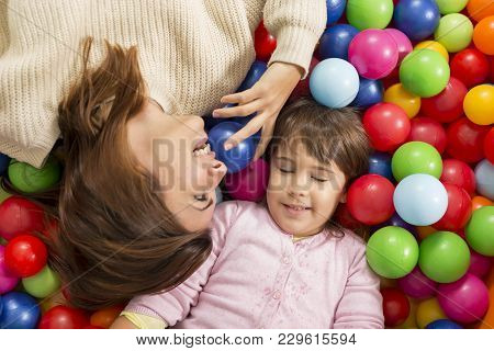 Top View Of Cheerful Mother And Daughter Playing In A Pool Filled With Colorful Balls. Focus On The