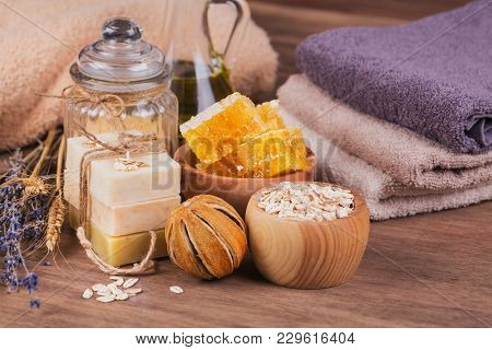 Honeycomb, Cosmetic Oil, Sea Salt, Oat And Handmade Soap With Honey On Rustic Wooden Background. Nat