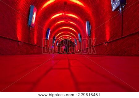 Red Corridor With Blueish Artwork. View From The Floor Level. Two People At The Far End.